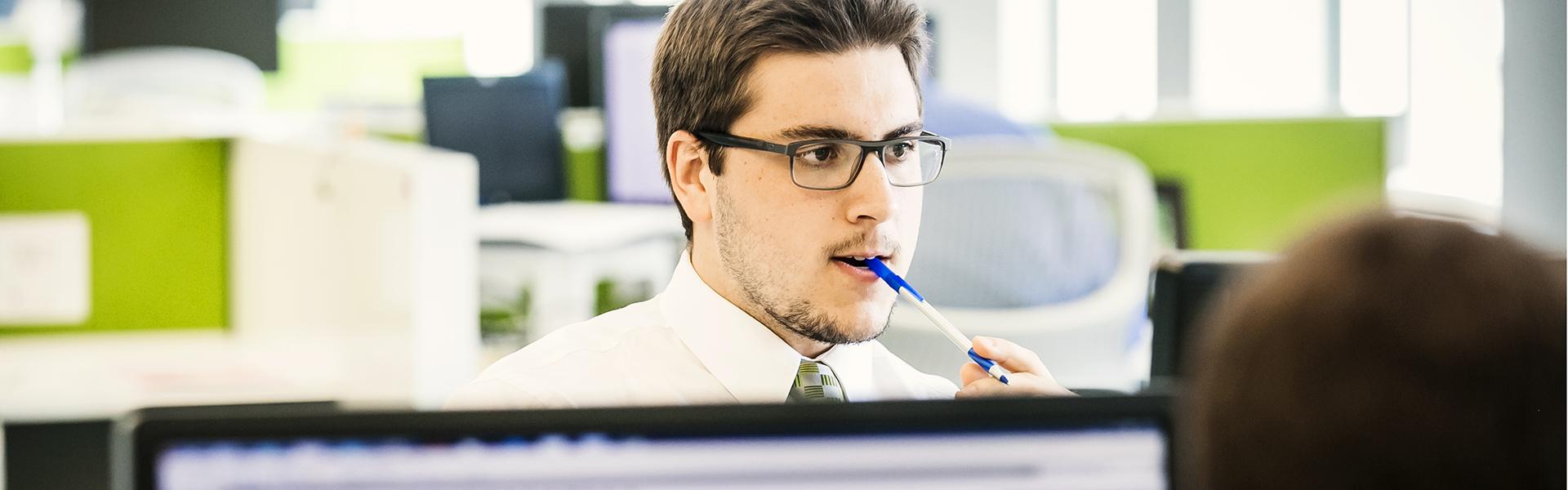 Étudiant au programme Techniques de comptabilité et gestion qui réfléchit en manipulant un stylo