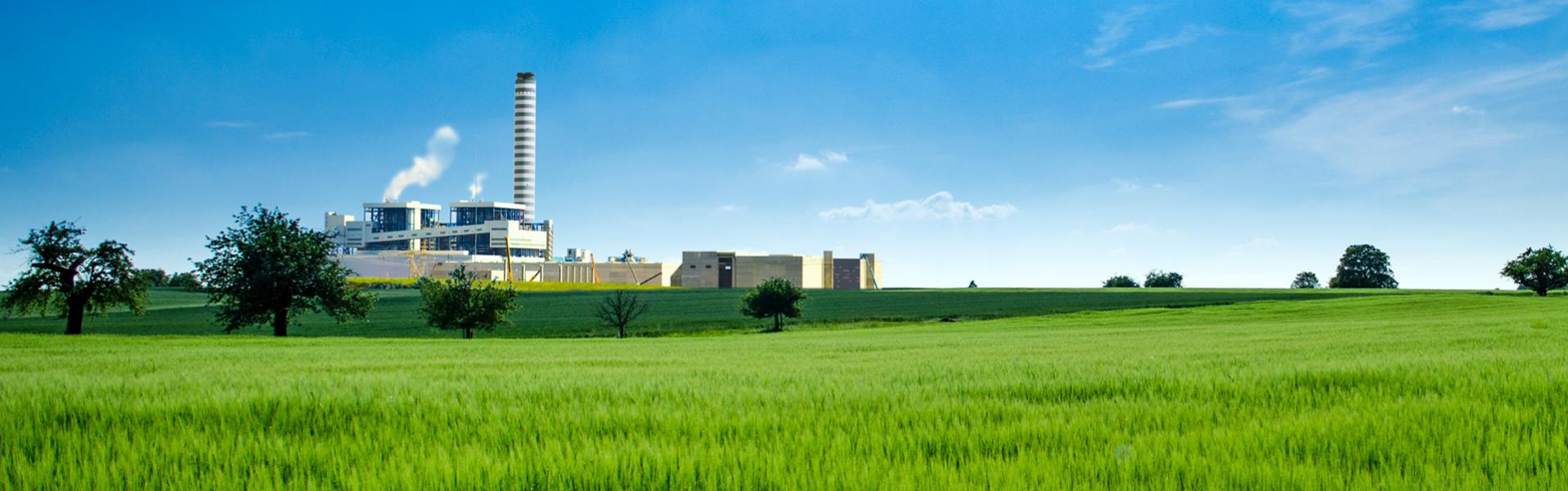 Une entreprise industrielle avec un champ d'herbes vertes au premier plan