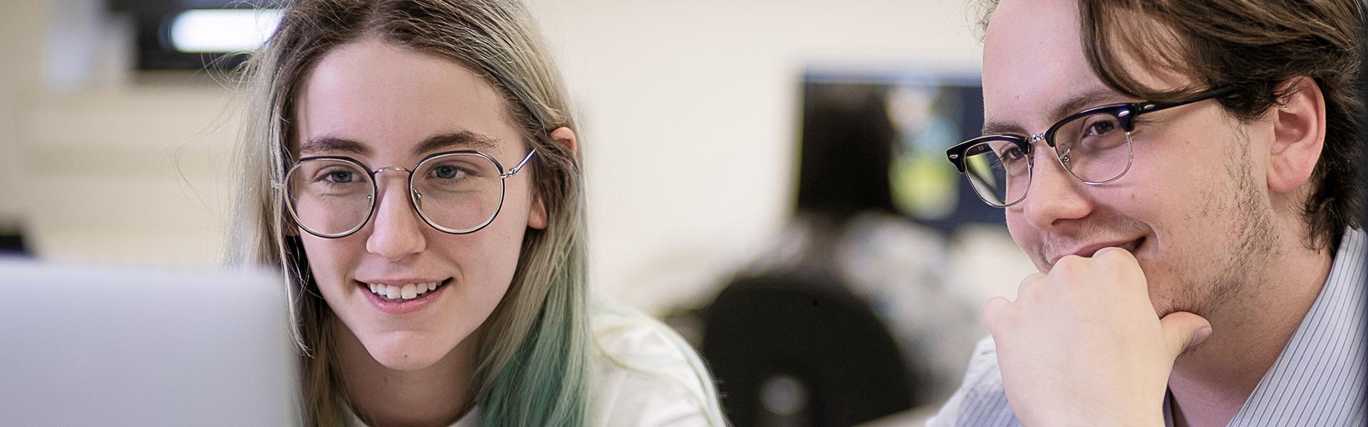 Étudiante et étudiant en graphisme devant un ordinateur