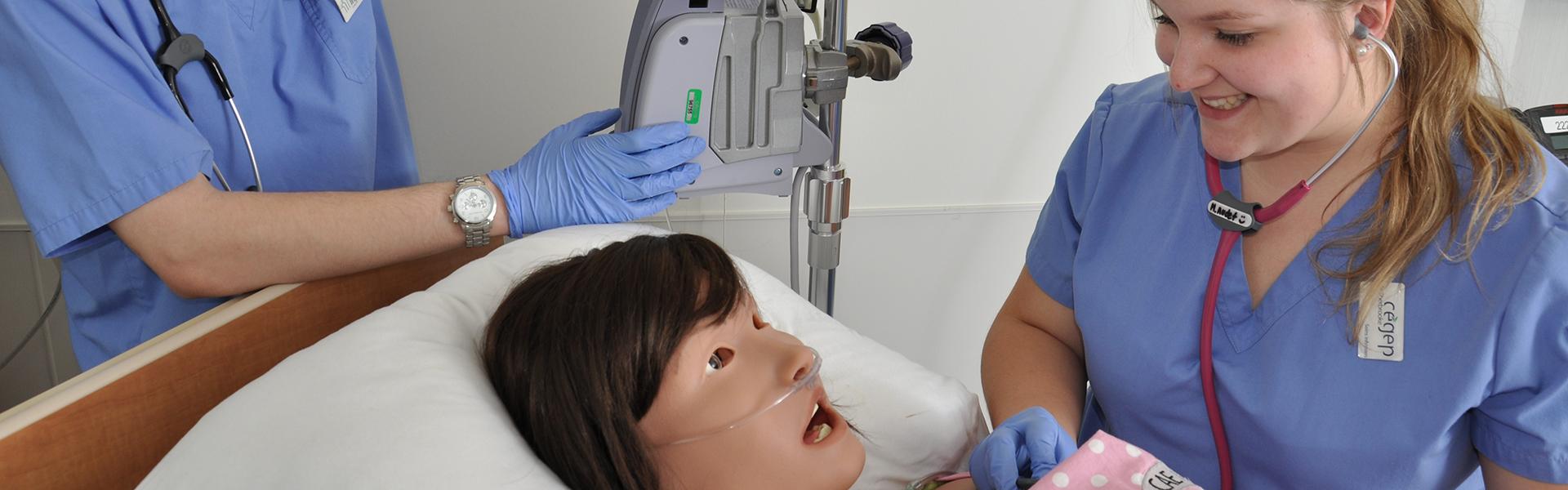 Étudiante en soins infirmiers avec mannequin simulateur