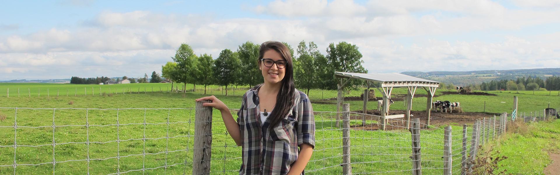 Étudiante du programme Gestion et technologies d'entreprise agricole devant la ferme-école