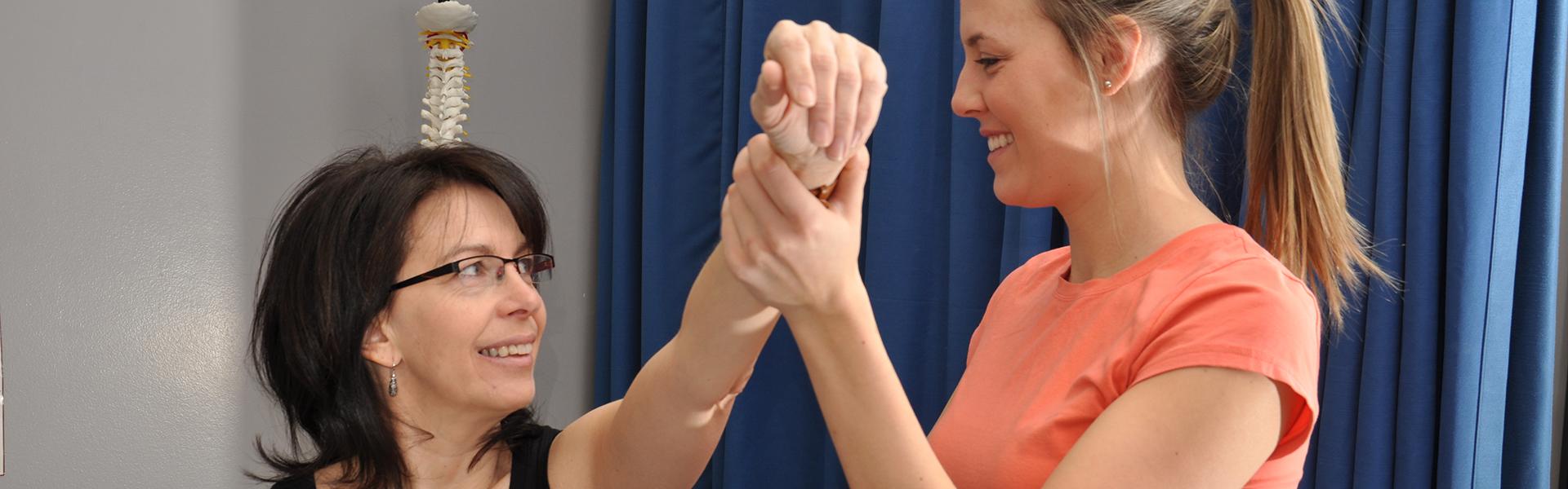 Étudiante et professeur en physiothérapie démontrant un exercice musculaire